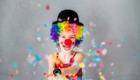 Bang! Funny kid clown playing at home. Child shooting party popper confetti. 1 April Fool's day concept