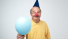 Happy mature man with red clown nose and blue ballon on birthday party.